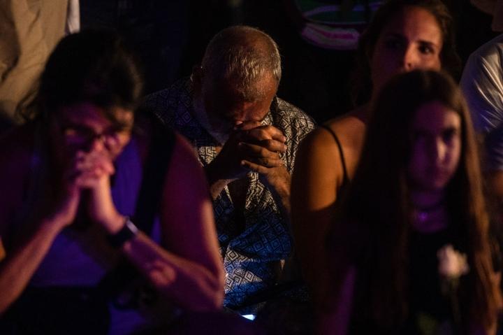 Ihmiset kokoontuivat Surfsidessa maanantaina paikallista aikaa muistamaan onnettomuuden uhreja. LEHTIKUVA / AFP