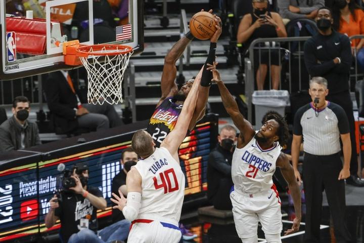 Voittokorin iski aivan ottelun loppuhetkillä Phoenixin Deandre Ayton (kuvassa keskellä).  LEHTIKUVA/AFP