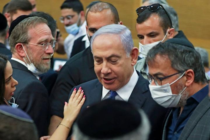 Tuoreen koalition huolena on, että Netanjahu (kuvassa keskellä) liittolaisineen pyrkii kaikin keinoin murentamaan haurasta hallitussopua. LEHTIKUVA / AFP