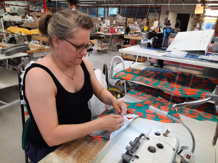 Ompelija Anne-Marie Tiilikainen ompelee Hertta-kuosillisia leggipöksyjä. Virkkukoukkusen tuotteita ommellaan päivittäin Kiteen tekstiilitehtaassa.