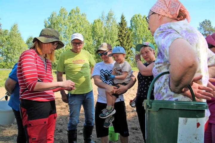 Reeta Rönkö (vas.) esittelee talkooväelle kukkapellon siemenseosta. Tälle pellolle Kesälahdelle tulee auringonkukkaa, hunajakukkaa, keltalupiinia ja rehuvirnaa.
