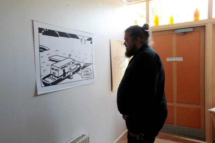 """""""Meriitit ovat ainakin tuoneet töitä."""" Tikkasen seinällä on esimerkki kuvituksista, joita hän tekee Iisalmen Sanomille."""
