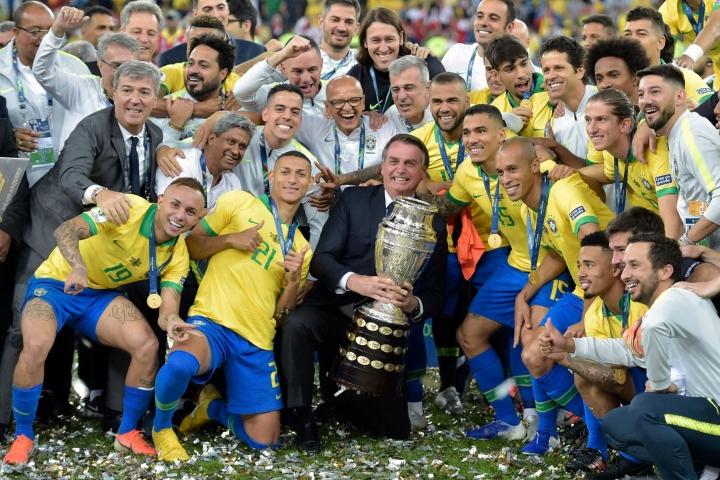 Kesältä 2019 olevassa kuvassa Brasialian presidentti Jair Bolsonaro pitää Copa America -maljaa juhlivien pelaajien ympäröimänä. Lehtikuva/AFP