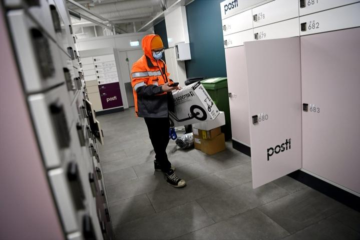 Postin työntekijä lajitteli paketteja automaattiin viime joulukuussa. Lehtikuva / Antti Aimo-Koivisto