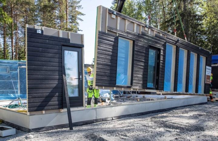 Elementeissä on ikkunat ja ovet valmiiksi asennettuina. Kirvesmies Arto Kinnunen seuraa suurelementin asettumista.