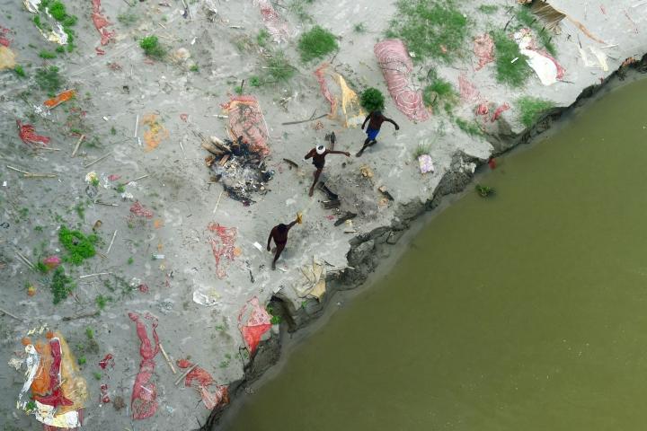 Intiassa Ganges-joki tulvii ja on huuhtonut esille satoja rannoilleen haudattuja koronauhreja. Kuvassa kalastajat kävelevät hautojen seassa. LEHTIKUVA/AFP