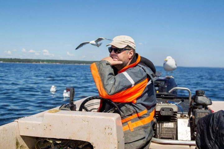Juha Metsäranta on kalastanut yli neljän vuosikymmenen ajan. Lokki on laskeutunut kyytiin perämoottorin kannen päälle.