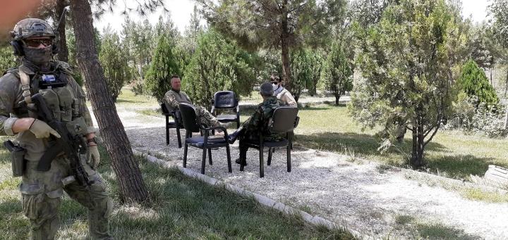 Eversti Joni Lindeman (istumassa vasemmalla) afganistanilaisen prikaatikenraalin ja paikallisen tulkin kanssa Afganistanissa heinäkuussa 2020. LEHTIKUVA/HANDOUT