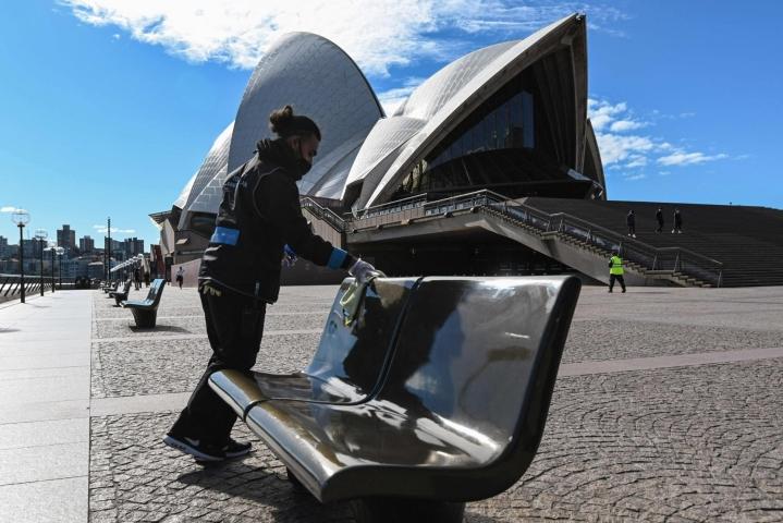 Sydney sulkeutui sisätiloihin. Työntekijä puhdistaa penkkejä Sydneyn oopperatalon edustavalla olevalla aukiolla. Lehtikuva/AFP