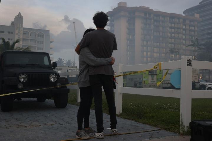 Ihmiset seurasivat perjantaina pelastustöitä romahtaneen kerrostalon raunioissa Floridan Surfsidessa. LEHTIKUVA / AFP