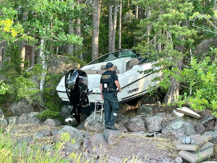 Porvoon Vessölandetissa rantakivikkoon törmännyt moottorivene jäi jumiin kahden puun väliin 19. kesäkuuta 2021. LEHTIKUVA / HANDOUT / RAJAVARTIOLAITOS