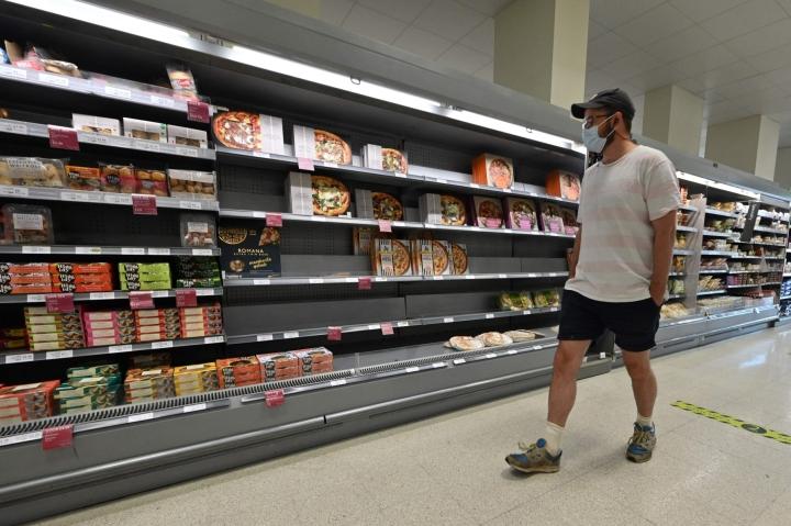 Britanniassa kaupoissa on tyhjiä hyllyjä, koska sekä kaupoissa että muualla tuotantoketjussa henkilökunnan jääminen kotiin korona-altistumisen vuoksi on haitannut työntekoa. LEHTIKUVA/AFP