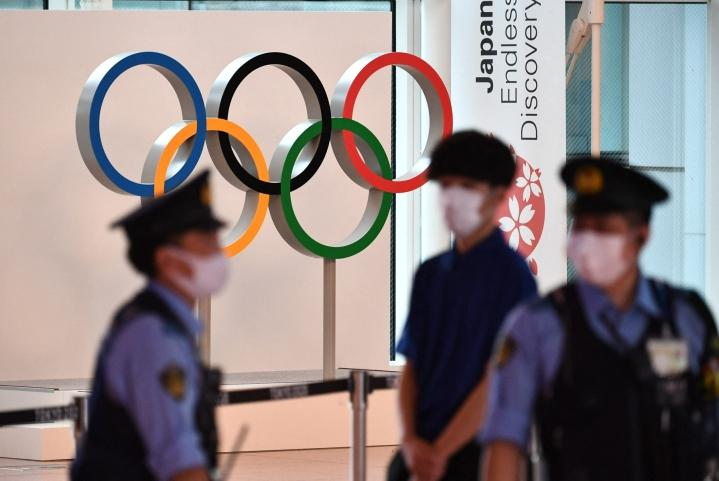 Olympiarenkaat poliisien taustalla Tokion kansainvälisellä lentoasemalla 8. heinäkuuta. LEHTIKUVA/AFP