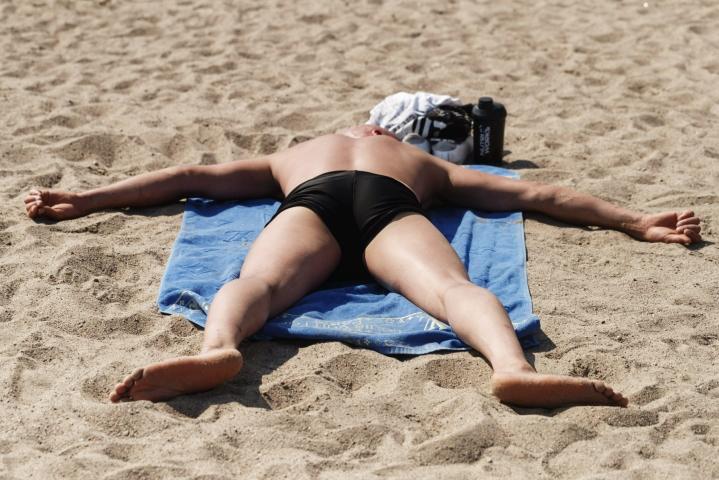 Helle ei ole kaikille hyväksi. Kuvassa auringonottaja Aurinkolahden uimarannalla Helsingissä. Lehtikuva / Roni Rekomaa