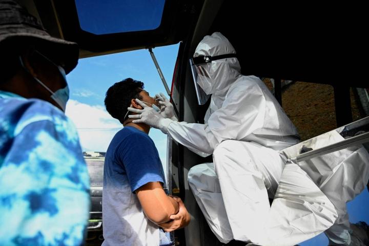 Terveydenhuollon työntekijä otti koronatestiä Lambarossa Acehin alueella Indonesiassa perjantaina. LEHTIKUVA/AFP