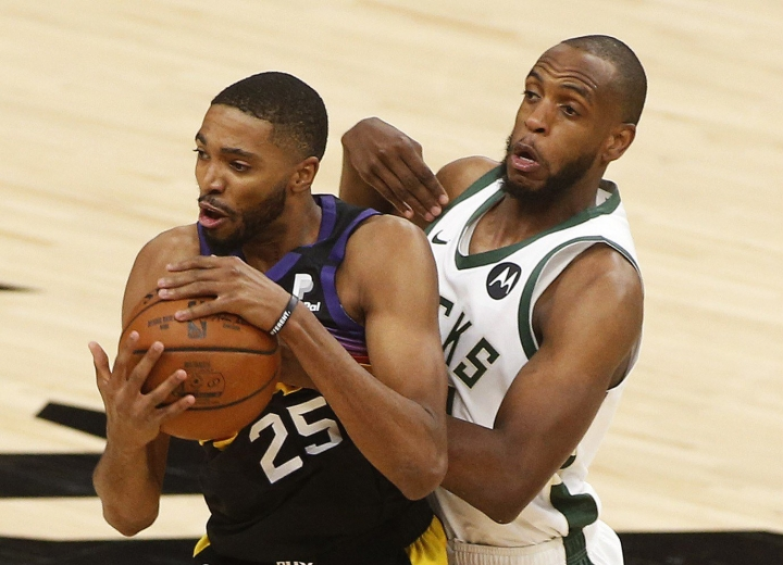 Milwaukee Bucksin Khris Middleton (oik.) tavoittelemassa palloa Phoenix Sunsin Mikal Bridgesin hyppysistä. LEHTIKUVA/AFP