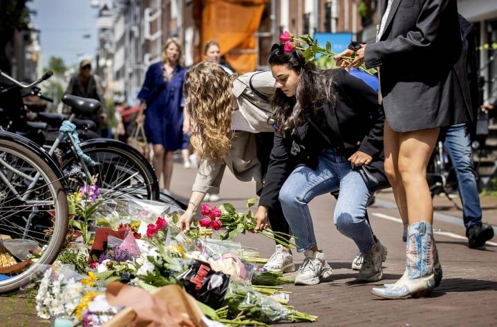 Amsterdamin keskustassa ohikulkijat ovat asettaneet kukkia, kynttilöitä ja tukiviestejä toimittaja Peter de Vriesille, jota ammuttiin lähietäisyydeltä useita kertoja tiistai-iltana. LEHTIKUVA / AFP