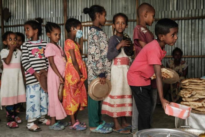 Tigrayn väkivaltaisuuksia paenneet lapset jonottivat vapaaehtoistyöntekijän tarjoamaa aamiaista. Lehtikuva/AFP