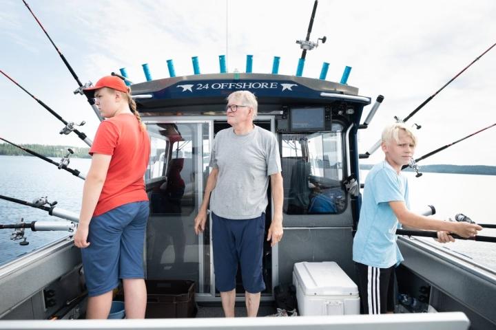 Amerikkalaisvalmisteinen vene sopii avomerelle ja tyynelle Höytiäiselle. Joel Honkonen (vas.), Kari Kakkonen ja Semi Koskinen kalastivat useammalla vavalla.