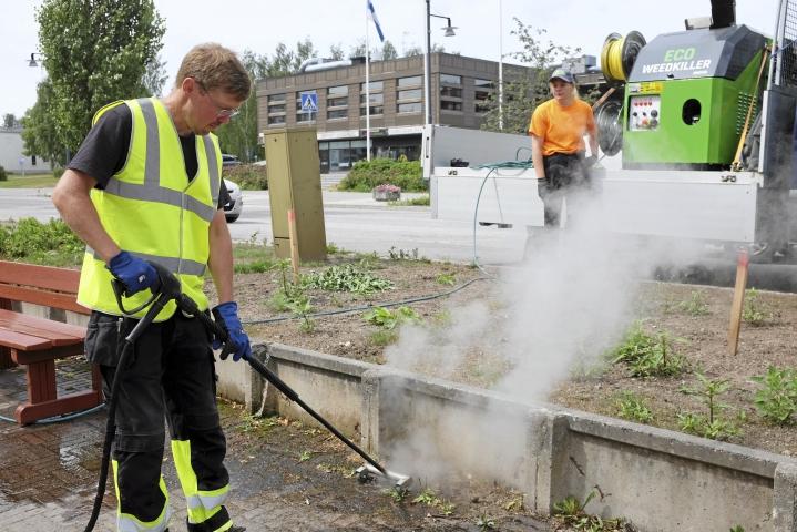 Voikukat nuupahtavat, kun puistotyöntekijät Hannu Tuokkola ja Melissa Jipp käsittelevät Nikkilän toria upouudella kuumavesikoneella.