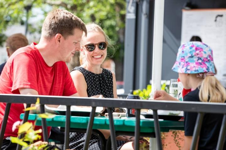 Mikko (vas.), Sanna ja Silja Mäkelä valitsivat Joensuun jokirannassa olevan ravintolan, johon puhaltava tuuli vilvoitti ruokailevaa perhettä.