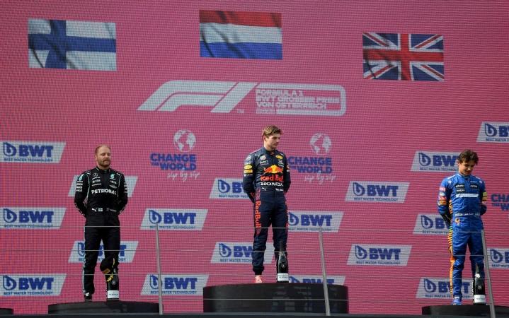 Palkintopallilla keskellä voittaja Max Verstappen, vasemmalla kisan kakkonen Valtteri Bottas ja oikealla kolmonen Lando Norris. LEHTIKUVA / AFP