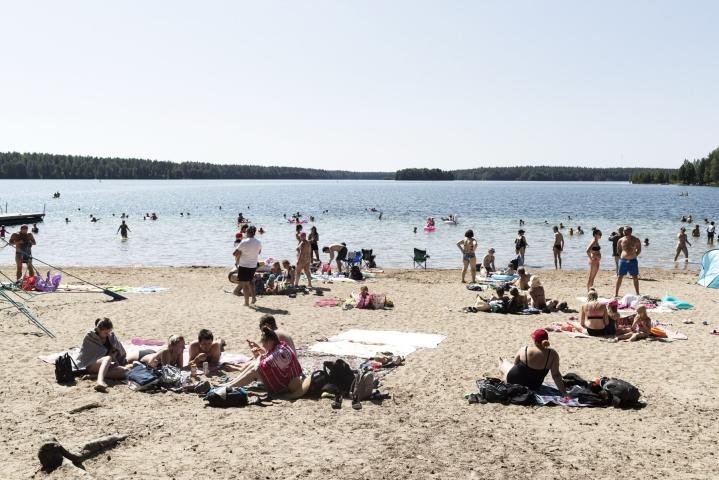 Sääksjärven rannalla Rajamäellä paistateltiin tänään auringossa. LEHTIKUVA / Roni Rekomaa