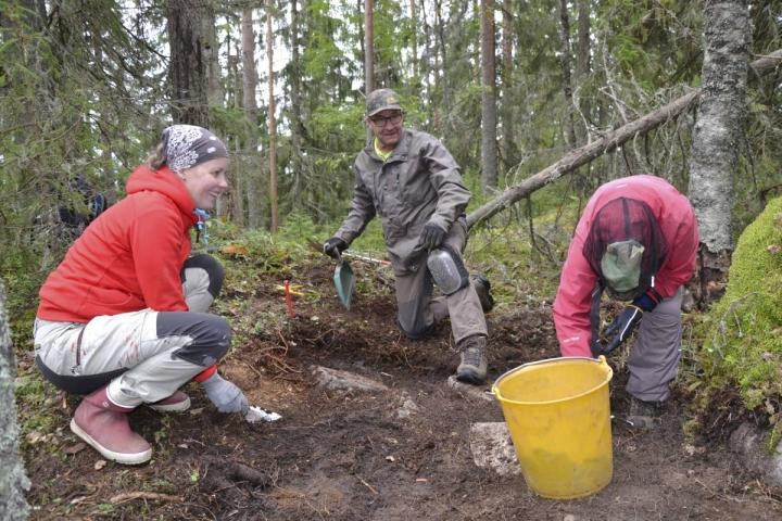 Outi Piiroinen (vas.) ja Caroline Kamppila sekä Johan Moraal kaivoivat esiin vanhaa hirsivarustuksen pohjaa, joka on tehty kivistä.