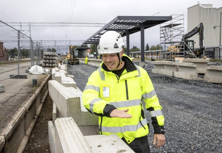 Väyläviraston Jetro Matilainen näyttää, kuinka korkealle uudet asemalaiturit tulevat suurin piirtein nousemaan.