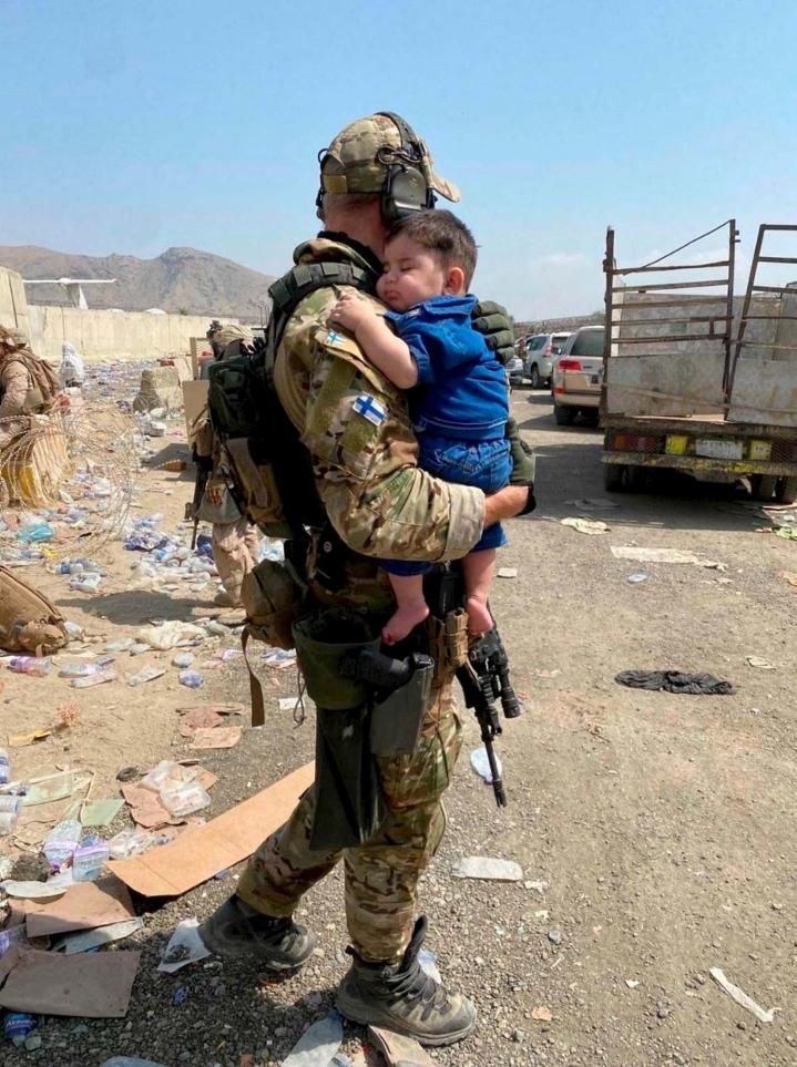 Suomalainen sotilas kantaa sylissään nukkuvaa lasta Kabulin lentokentällä. LEHTIKUVA / handout / Puolustusvoimat