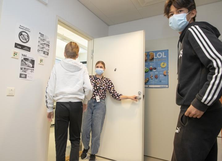 Kouluterveydenhoitaja Anne Hoskonen ottaa oppilaita yksi kerrallaan vastaanotolle. Oikealla Aaro Hwang jää vielä odottelemaan, kun Sampo Laakkonen käy rokotuksessa.