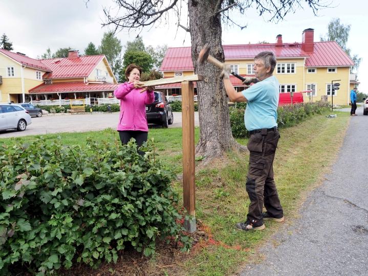 Tuula Kupiainen ja Arto Arvekari pystyttävät tolppaa Sovintolan pihasta lähtevälle kulttuurireitille.
