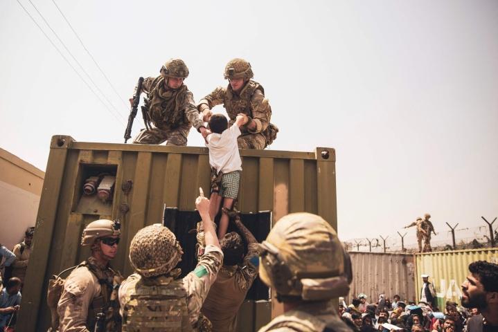 Yhdysvaltain merijalkaväen sotilaat avustavat evakuoitavaa lasta Kabulin lentokentällä.  LEHTIKUVA / AFP / US Marine Corps / Staff Sgt. Victor Mancilla