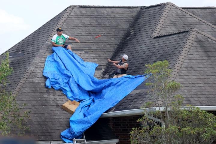 Vaurioitunutta kattoa peitettiin Laplacessa Louisianassa. Lehtikuva/AFP