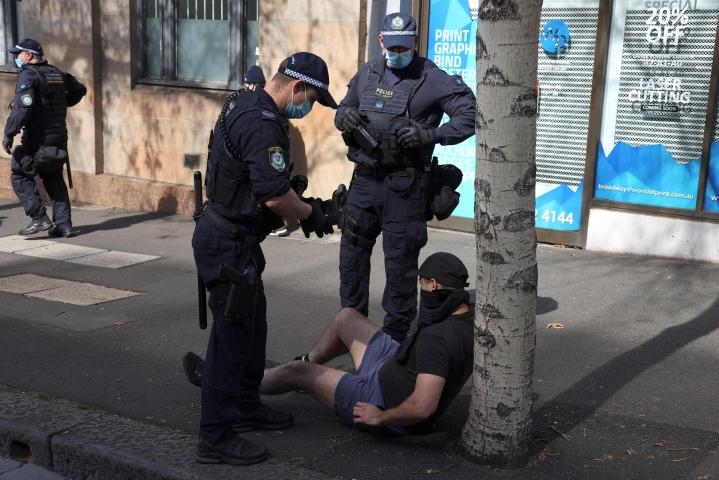 Australian Melbournessa koronasulkua vastustavat mielenosoittajat ovat ottaneet yhteen poliisin kanssa. Kuva on lauantailta Sydneystä, jossa poliisi on myös pidättänyt mielenosoittajia. LEHTIKUVA/AFP