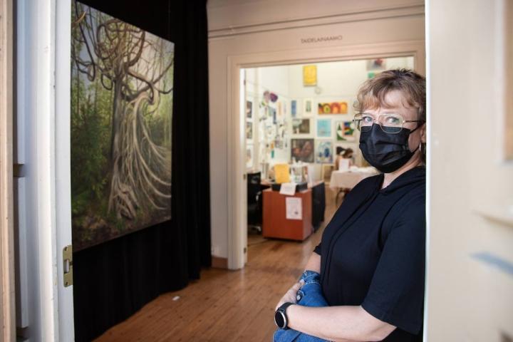 Pia Saari kaipaa usein luontoon. Taustalla on hänen Loitsu-teoksensa.