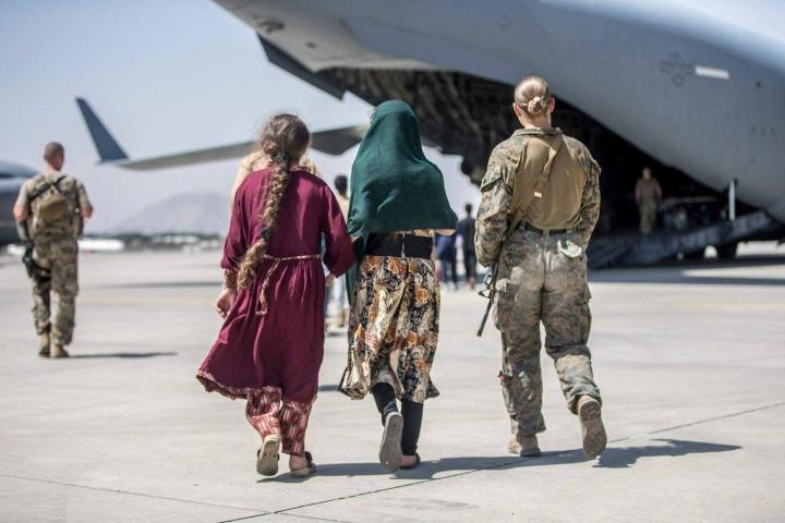 Amerikkalaissotilas saatteli tiistaina evakuoituja koneeseen Kabulin lentokentällä. Kuvan henkilöt eivät liity juttuun.