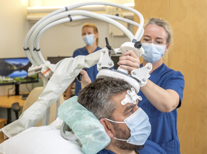 Aivojen magneettistimulaatiohoito (rTMS) sopii lievän ja keskivaikean masennuksen hoitoon. Sairaanhoitaja Johanna Vaittinen asettelee malliksi laitetta toisen sairaanhoitajan Jarno Lehikoisen päähän. Taustalla on ylilääkäri Raija Soikkeli.