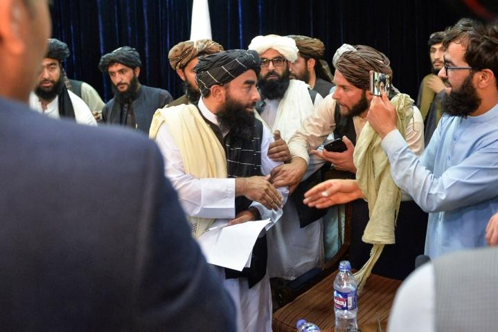 Suomalaistutkijan mukaan Talebanin viestinnässä on suurelta osin kyse ulkomaailmalle suunnatusta hymykampanjasta. Talebanin tiedottaja Zabihullah Mujahid (keskellä) piti tiistaina tiedotustilaisuuden Kabulissa. LEHTIKUVA / AFP