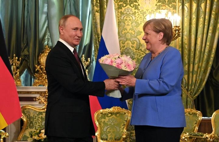 Putinilta kukkakimpun tervetuliaisiksi saanut Merkel aloitti perjantain keskustelut sovinnolliseen sävyyn. LEHTIKUVA / AFP