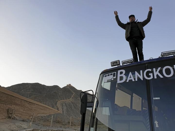 Jani Laine voitonriemuisena bussin katolla, taustalla Kiinan muuri.