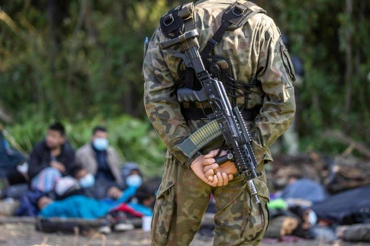 Puolalaissotilas vartioi rajalle tullutta turvapaikanhakijaryhmää Usnarz Gornyssa, Valko-Venäjän rajalla.