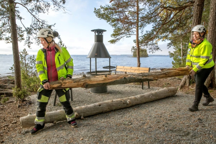 Puistosuunnittelija Paula Lamminsalo ja työnjohtaja Heidi Keskitalo siirtävät pois viime esteitä Kalmoniemen tulipaikalla, joka on mahdollisimman tasainen ja avara lähestyä myös apuvälineitä käyttäville.