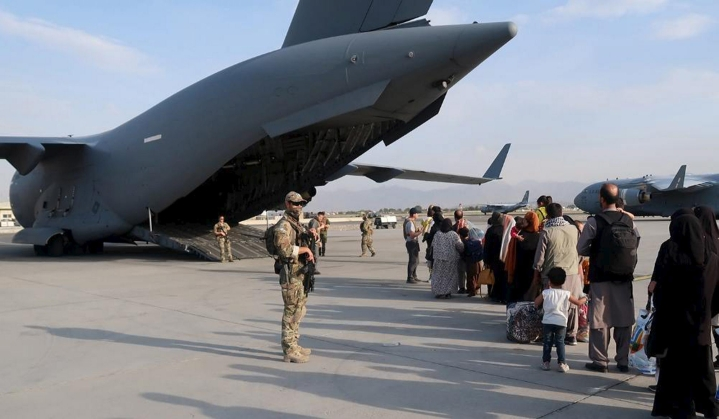 Puolustusvoimien suojausjoukon sotilaita ja evakuoitavia ihmisiä Kabulin lentokentän alueella päiväämättömässä kuvassa. LEHTIKUVA / HANDOUT / PUOLUSTUSVOIMAT