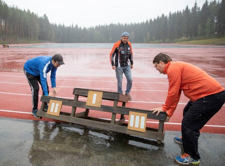 Hammaslahden urheilukentällä on nyt pinnoite koko 350 kierroksen radalla. Pyhäselän Urheilijoiden puheenjohtaja Petri Stenberg (oik.), yleisurheilujaoston puheenjohtaja Eero Könönen sekä nuorisovalmennuspäällikkö Anssi Vänskä iloitsevat parantuneista olosuhteista, vaikka maanantaina satoikin vettä niskaan.