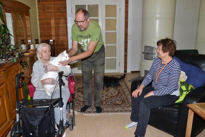 Viihtyisässä olohuoneessa Aino Martiskainen silittää terapiakissa Novaa, jonka Juha Timonen kertoo käyvän jokaisen asukkaan huoneessa loikoilemassa. Oikealla Anita Timonen.