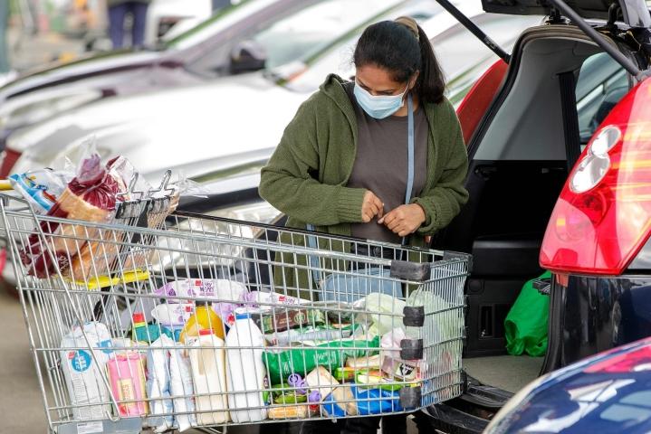 Aucklandiin jää voimaan tiukkoja rajoitustoimia vielä vähintään viikon ajaksi. Kasvomaskia käyttävä nainen purki ostoksiaan vuosi sitten Takapunan lähiössä Aucklandissa. LEHTIKUVA/AFP