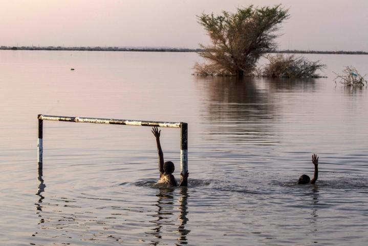 Ihmisiä tulvavesissä Sudanin pääkaupunki Khartumissa syyskuussa. LEHTIKUVA / AFP