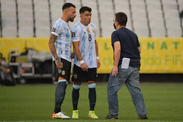 Terveysvirkailija väitteli Argentiinan Nicolas Otamendin (vas.) ja Marcos Acunan kanssa. LEHTIKUVA / AFP