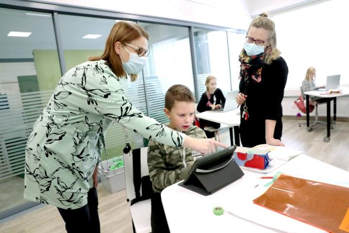 Kontioniemen koulun johtaja Sanna Huovinen (vas.) ja erityisopettaja Tuula Puruskainen neuvovat kakkosluokkalaista Aapo Haarasta tehtävissä.